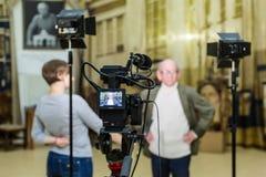 Das Mädchen interviewt den Mann Videodreh im Innenraum Lcd-Anzeige auf dem Kamerarecorder lizenzfreie stockbilder