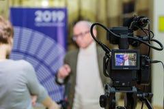 Das Mädchen interviewt den Mann Videodreh im Innenraum Lcd-Anzeige auf dem Kamerarecorder stockfotografie