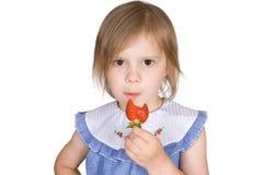 Das Mädchen isst eine Erdbeere Stockfotografie