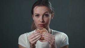 Das Mädchen isst einen Burger Lokalisiertes Schwarzes Porträt stock footage