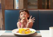 Das Mädchen isst Gemüse und zeigt fünf Finger lizenzfreie stockfotografie