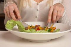Das Mädchen isst Salat Stockfoto