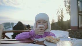 Das Mädchen isst zu Mittag Glückliches Mädchen mitten in schneebedeckten Bergen Der Junge gelegt auf den Schnee stock footage