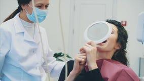 Das Mädchen ist an der Aufnahme am glücklichen Kunden des Zahnarztes A am Zahnarztlächeln Zahnmedizinische Bleiche Zahnmedizinisc stock footage