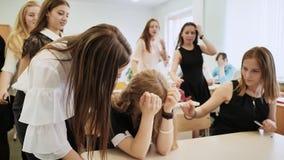 Das Mädchen ist ein Schulmädchen, das in der Klasse schreit und ihre Mitschüler trösten sie stock video footage