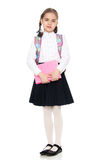 Das Mädchen ist ein Schulmädchen mit einem Buch in ihren Händen Stockbild