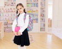 Das Mädchen ist ein Schulmädchen mit einem Buch in ihren Händen Stockfoto