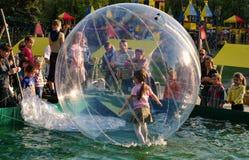 Das Mädchen ist in einem transparenten aufblasbaren Ballon auf dem Wasser auf dem Spielplatz in Kiew Lizenzfreie Stockbilder