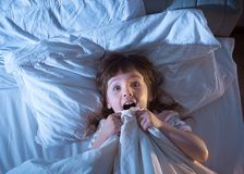 Das Mädchen ist erschrockenes Lügen im Bett Lizenzfreie Stockfotografie