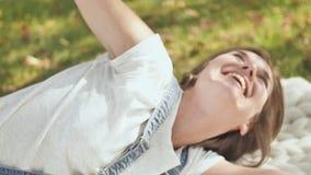 Das Mädchen ist glücklich, weil sie sie Wünsche erfüllte Lügen im Sommer im Park auf einem Merinoplaid stock video footage