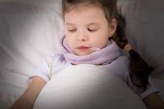 das Mädchen ist krank und betrachtet den Thermometer beim Lügen im Bett lizenzfreies stockbild