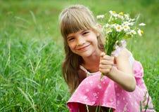 Das Mädchen ist lächelnd anhalten und einen Blumenstrauß Lizenzfreies Stockfoto