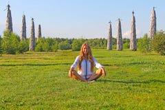 Das Mädchen ist, lächelnd sitzend und auf dem grünen Gras Lizenzfreies Stockfoto