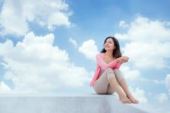 Das Mädchen ist sehr bequem und frei und sitzt über dem beautifu stockfoto
