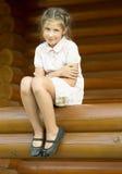 Das Mädchen ist sittind auf einem Klotz Lizenzfreie Stockbilder