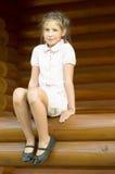 Das Mädchen ist sittind auf einem Klotz Lizenzfreie Stockfotos