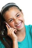 Das Mädchen ist, sprechend lachend und durch Telefon Stockfoto