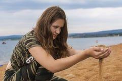 Das Mädchen ist unter dem Spielen mit Sand stockbild