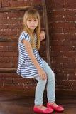 Das Mädchen 6 Jahre alt in den Jeans und in der Weste sitzt auf einer Leiter nahe Wand Stockbilder