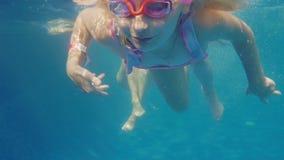 Das Mädchen 6 Jahre alt lernt, im Pool zu schwimmen Ihre Mutter hilft ihr Unerkannter Taucher steigt auf der Oberfläche stock video footage