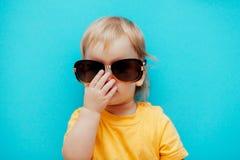 Das Mädchen justiert ihre Sonnenbrille auf der Brücke Ihrer Nase stockbild
