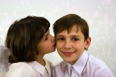 Das Mädchen küßt den Bruder auf einer Backe Lizenzfreies Stockfoto