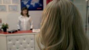 Das Mädchen kam zum Cosmetology, wird sie herzlich vom Doktor gegrüßt, sagt etwas und bittet, einige Dokumente zu unterzeichnen stockbilder