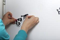 Das Mädchen klebt die herausgeschnittenen Elemente vom selbstklebenden Papier, um die Defekte der weißen Tür zu maskieren Stockfotos