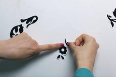 Das Mädchen klebt die herausgeschnittenen Elemente vom selbstklebenden Papier, um die Defekte der weißen Tür zu maskieren Lizenzfreie Stockfotos