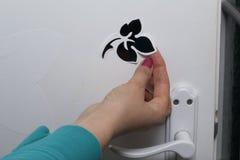 Das Mädchen klebt die herausgeschnittenen Elemente vom selbstklebenden Papier, um die Defekte der weißen Tür zu maskieren Lizenzfreies Stockfoto