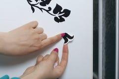 Das Mädchen klebt die herausgeschnittenen Elemente vom selbstklebenden Papier, um die Defekte der weißen Tür zu maskieren Stockbild