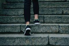 Das Mädchen klettert auf konkreter Treppe stockfotografie