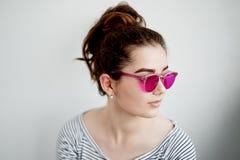 Das Mädchen lächelt glücklich in den rosa Gläsern Eine naive Ansicht der Welt im Übergang zum Erwachsensein stockbild
