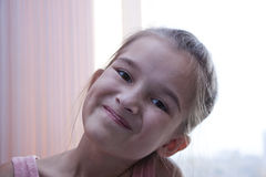 Das Mädchen lächelt morgens am Fenster Stockfotos