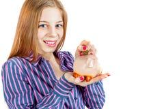 Das Mädchen lässt die Münze in das Sparschwein fallen lizenzfreies stockbild