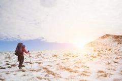Das Mädchen läuft den Schnee in den Bergen durch Stockfotografie