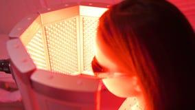 Das Mädchen läuft einen Kurs der Hautverjüngung mithilfe der roten hellen Behandlung durch stock footage