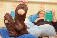 Das Mädchen liegt auf Couch und liest ein Buch, im Vordergrund die holey Socken stockfotos