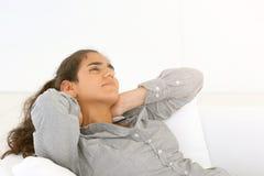 Das Mädchen liegt auf der entspannenden Couch stockfoto