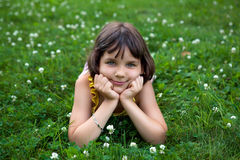 Das Mädchen liegt auf einem grünen Rasen. Lizenzfreie Stockfotografie