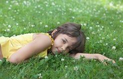Das Mädchen liegt auf einem Rasen. Lizenzfreies Stockfoto