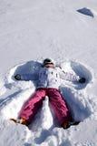 Das Mädchen liegt auf Schnee. Schneengel Lizenzfreies Stockfoto