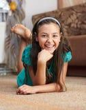 Das Mädchen liegt der Teppich Stockbilder