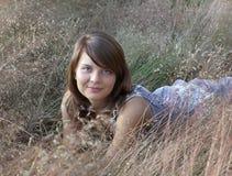 Das Mädchen liegt im nicht schiefen Gras Lizenzfreie Stockbilder