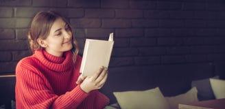Das Mädchen liest ein Buch in einem Café stockbilder
