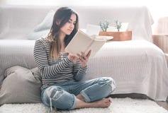Das Mädchen liest im Wohnzimmer lizenzfreie stockfotos