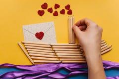 Das Mädchen macht ein Geschenk mit ihren eigenen Händen in Form eines Schiffs von Bleistiften und sendet einen Brief mit einem He Lizenzfreie Stockfotografie