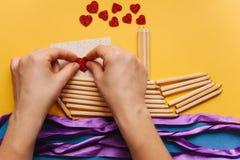 Das Mädchen macht ein Geschenk mit ihren eigenen Händen in Form eines Schiffs von Bleistiften und sendet einen Brief mit einem He Lizenzfreie Stockfotos