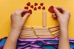 Das Mädchen macht ein Geschenk mit ihren eigenen Händen in Form eines Schiffs von Bleistiften und sendet einen Brief mit einem He Lizenzfreies Stockfoto