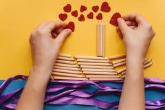 Das Mädchen macht ein Geschenk mit ihren eigenen Händen in Form eines Schiffs von Bleistiften und sendet einen Brief mit einem He Stockfoto